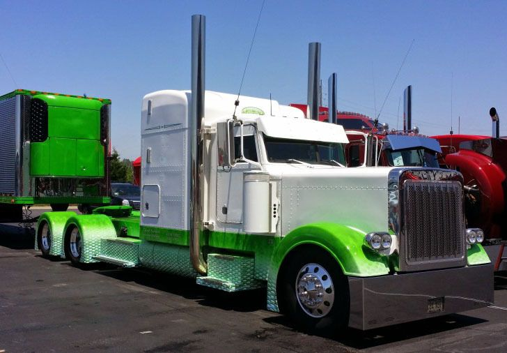 Green and white tractor trailer show truck