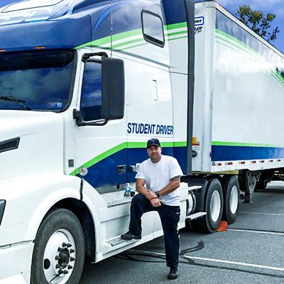 studen truck driver standing in front of his truck